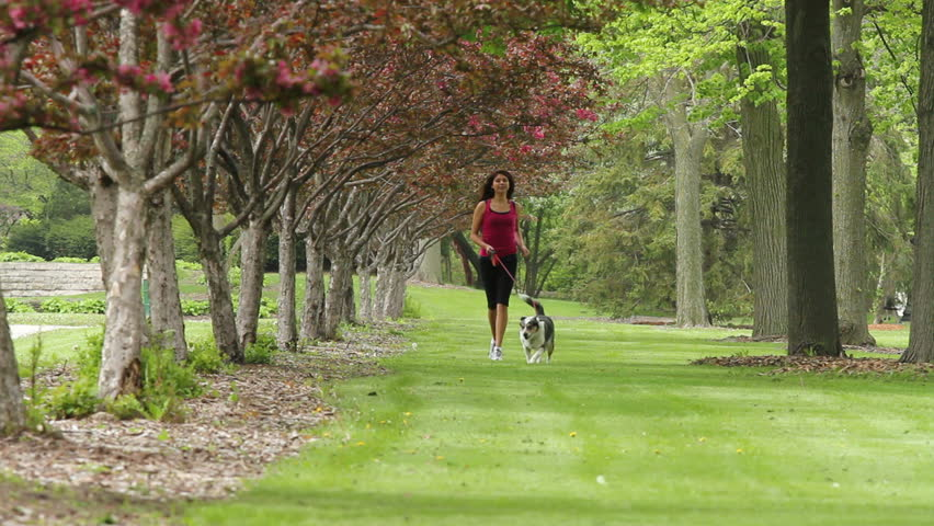 Woman jogging in the grass with her dog