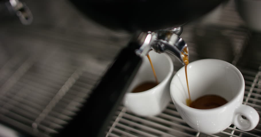 Super slow motion of hot espresso coffee pouring into a two white porcelain cups from coffee machine in 4k ( top view close up) #11972216