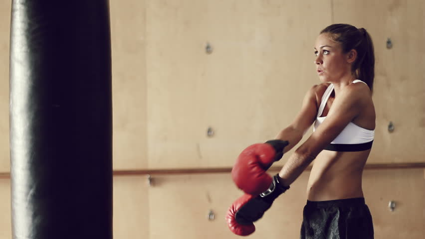 Beautiful Young Female Athlete Exercising For Self Defense With Boxing Gloves And Body Bag In Gym