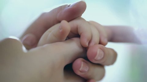 Concept of love and family. hands of mother and baby closeup, Hand in hand. Mother care. Caring mother with baby, Playing with baby. Slow Motion.