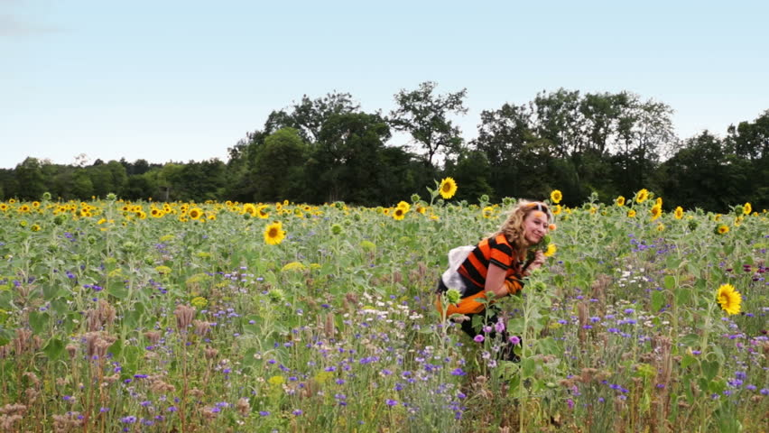 Woman in bee costume in a meadow with sunflowers, is dancing and having fun, smelling on the flowers | Shutterstock HD Video #12007292