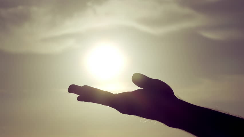 Grasping the sun with palm/fingers slow motion.100fps-25fps conformed slow motion shot of a silhouetted male hand against a sun and sky background, grasping the sun and letting sunlight pass through. #12056102