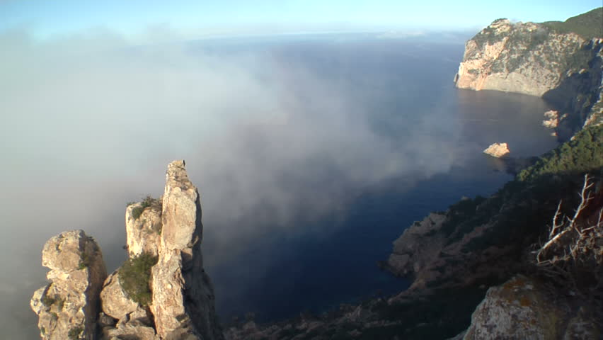 timelapse of a foggy & rugged cliff over the sea, wiht some trees on the right, a big rock boulder on the left