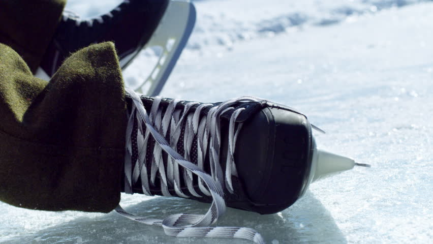 A close up shot of a hockey skate on an outdoor ice rink with a quick motion of beginning to tie the laces.