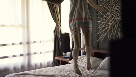 Woman legs jumping on bed, super slow motion, 240fps