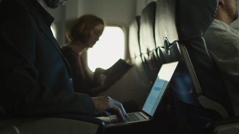Young man is working on a laptop on an airplane and a woman is reading in the background next to a window. Shot on RED Cinema Camera in 4K (UHD).