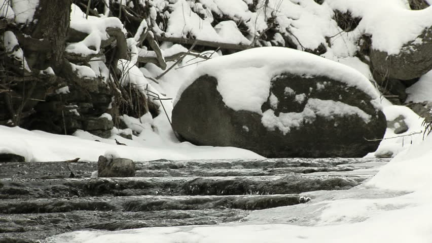 Stream and waterfall after snowfall with large rock in middle of stream.