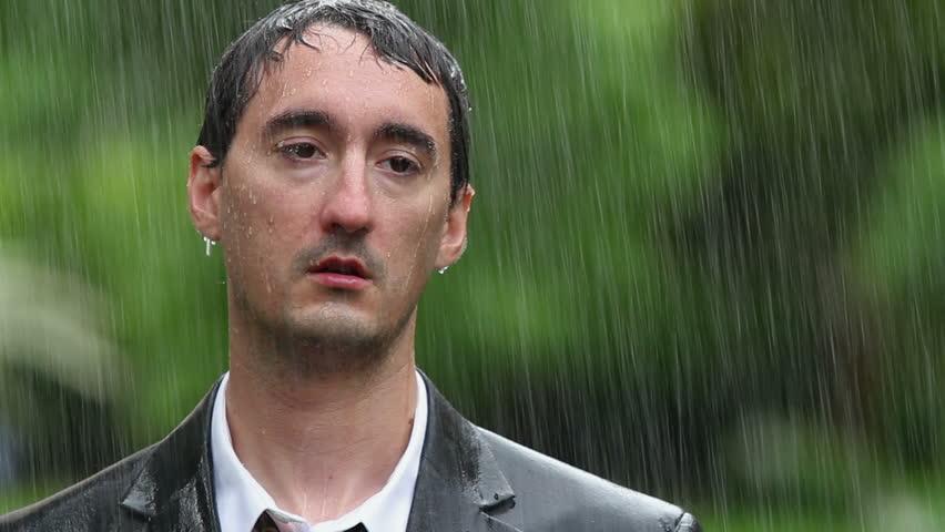 Man wearing suit standing in rain