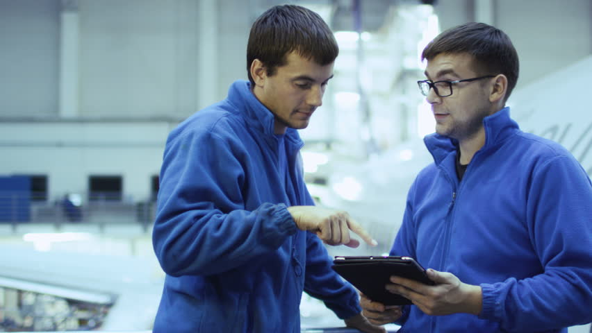 Two aircraft maintenance mechanics have a conversation while using a tablet in a plane hangar. Shot on RED Cinema Camera in 4K (UHD).
