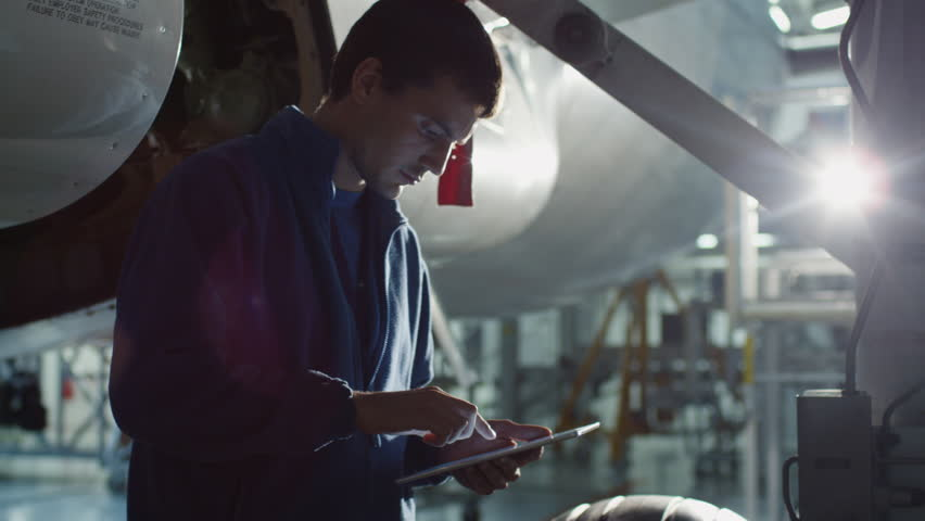 Aircraft maintenance mechanic uses tablet to inspect plane chassis in a hangar. Shot on RED Cinema Camera in 4K (UHD).
