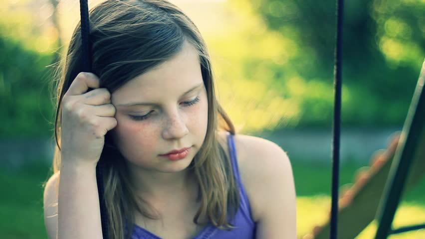 Sad preteen girl sitting on swing