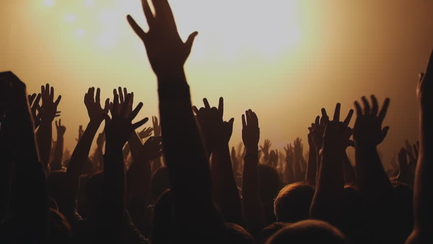 Lot of people clapping at rave party. Here is  footage of people crowd partying at a concert or a night club. You can see dark silhouettes dancing, jumping and waving hands in front of stage.