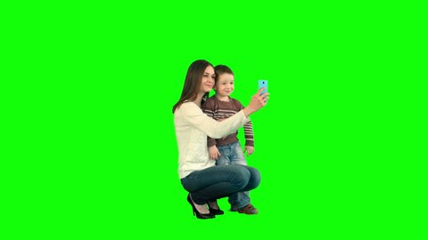 Mother And Son Posing For Selfie  on a Green Screen, Chroma Key. Professional shot on BMCC RAW with high dynamic range. You can use it e.g in your commercial video, family video, music video.