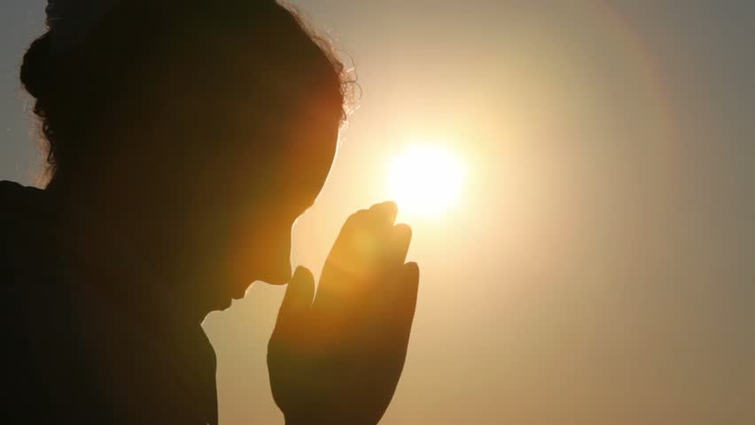Silhouette of woman head with sunshine behind, she is praying | Shutterstock HD Video #1222372