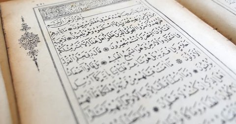 4K footage of a person reading from an old Quran...