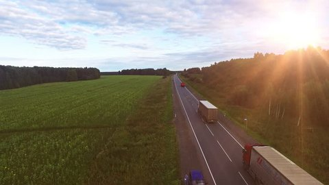 Aerial view of Truck on the road with sunset in the background. Large delivery truck is moving towards setting sun.