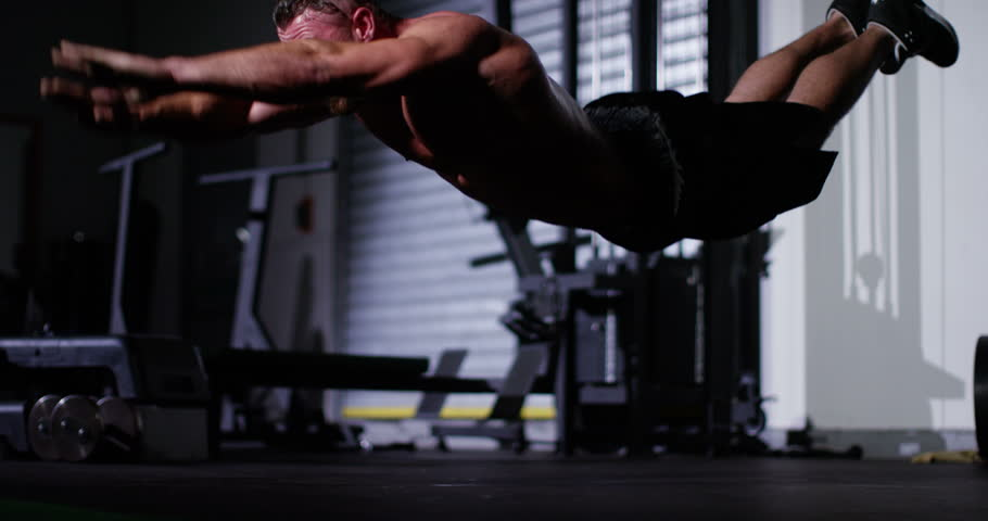 An athlete doing extreme push ups at a gym. Shot on RED Epic.