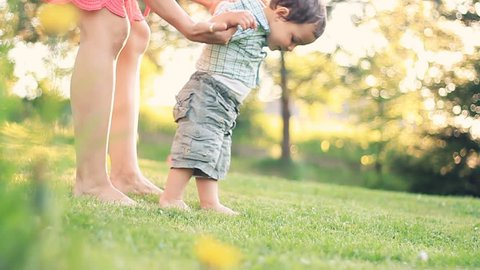 Baby first steps on grass, slow motion, dolly shot