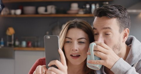 Happy couple at home in kitchen at breakfast using smartphone together browsing online having fun drinking coffee