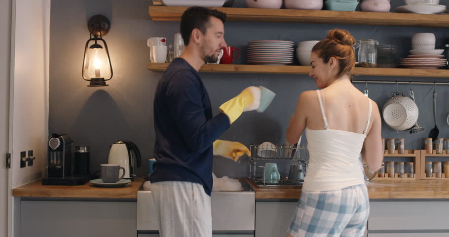 Couple washing dishes dancing at home wearing pajamas having fun laughing