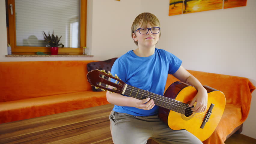 Young man hold guitar and look in camera 4K. Wide slide shot of boy with guitar posing in front of camera. Shoot in living room with window and sofa in background. | Shutterstock HD Video #12315452
