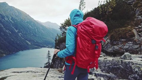 Hiker woman walking with backpack admiring mountain lake view landscape from the cliff edge. Stabilized, Slow Motion 120 fps. Epic Steadicam hiking in a stormy wind. Misty Mountains Series.