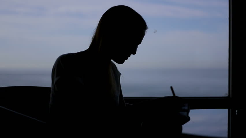 Silhouette of young beautiful girl sits in a cafe with panoramic window sea view . Morning, with a book, notepad, wrighting, thinking | Shutterstock HD Video #12339662