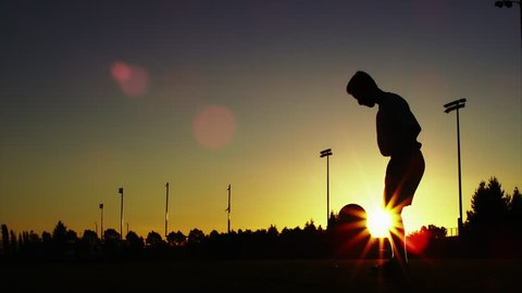 Silhouette of a soccer player juggling a ball