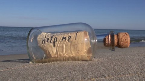 Vintage bottle with a message on ocean beach - help me