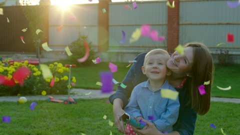 Mother and her little son are exploding party cracker on the backyard and merrily watching at falling confetti.
