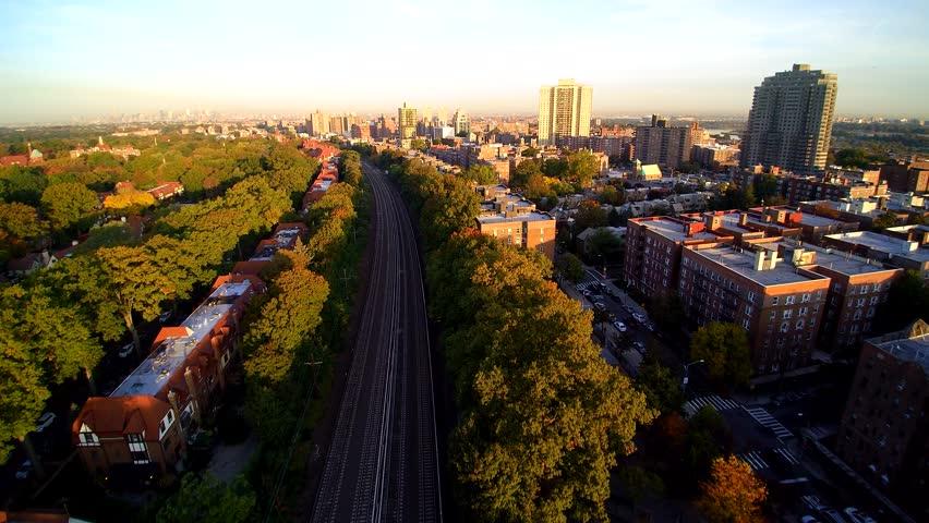 Queens NY train speeds to Manhattan morning 4k AERIAL