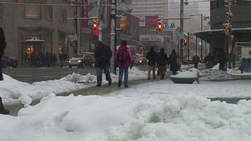 A busy downtown intersection in the middle of a snow storm.
