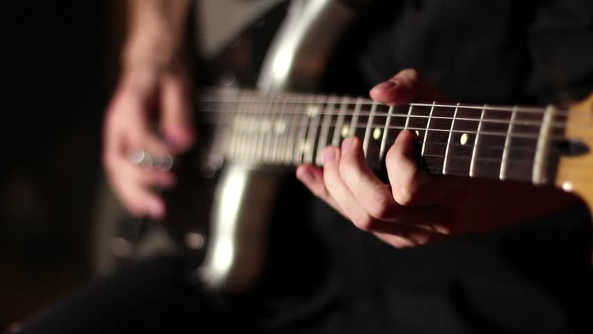 Electric guitar. Gray-black guitar. Musician plays rock music. The energetic game of rock style. Black background. Fast guitar solo. Six strings. Pluck the strings. Game mediator. Rock and roll.