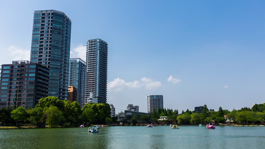 Clouds roll through past the Tokyo skyline in the 4K UHD time-lapse of people riding boats around a lake in Ueno. Shot on a sunny afternoon in the summer in Japan.