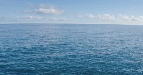 Aerial Shot Revealing Beautiful Sunny Ocean Landscape. Flying Low Over Green Grass Field Off Sea Cliffs. Shot in 4K