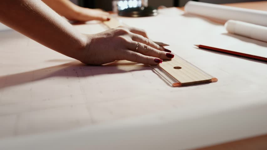 University student of Interior Design doing homework, completing housing project for final exam. The girl draws lines on a blueprint with a ruler in her studio. Closeup, dolly shot