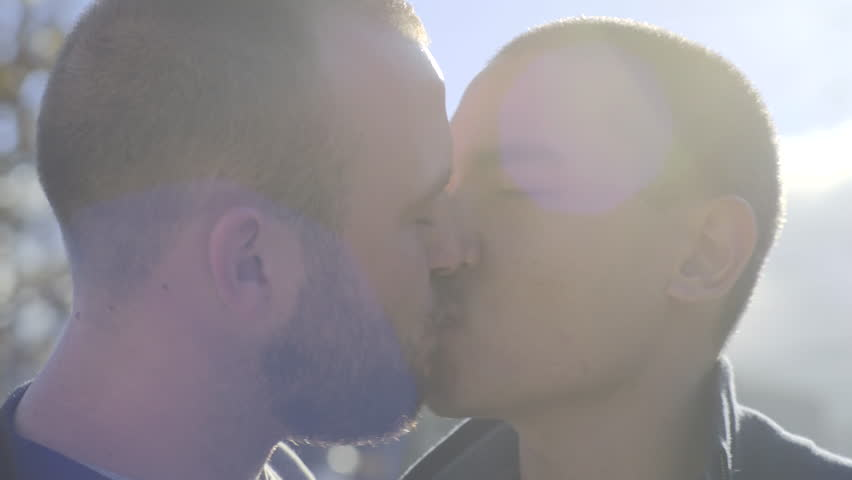 Closeup Of Interracial Male Couple, They Kiss, Gay Pride Flag In Background