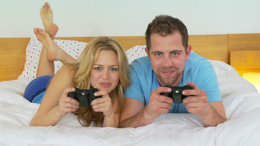 Young couple playing video games in bed