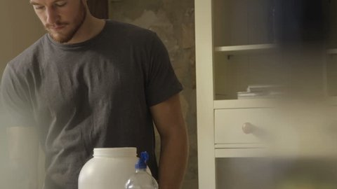 Slow motion clip of a young man making a protein shake at home