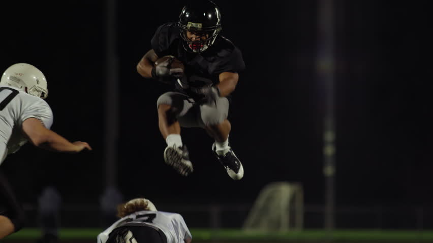 A football player jumps over his opponents to make a touchdown, slow motion