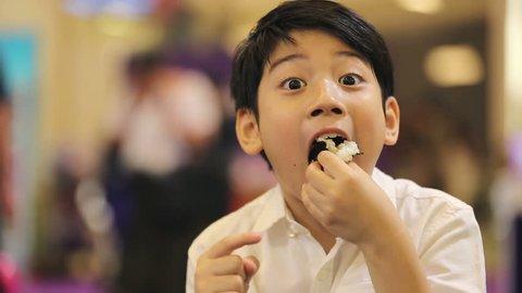 Happy asian boy eating japanese food.