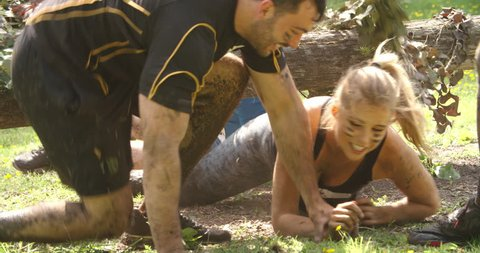 Competitors help each other through net on an assault course