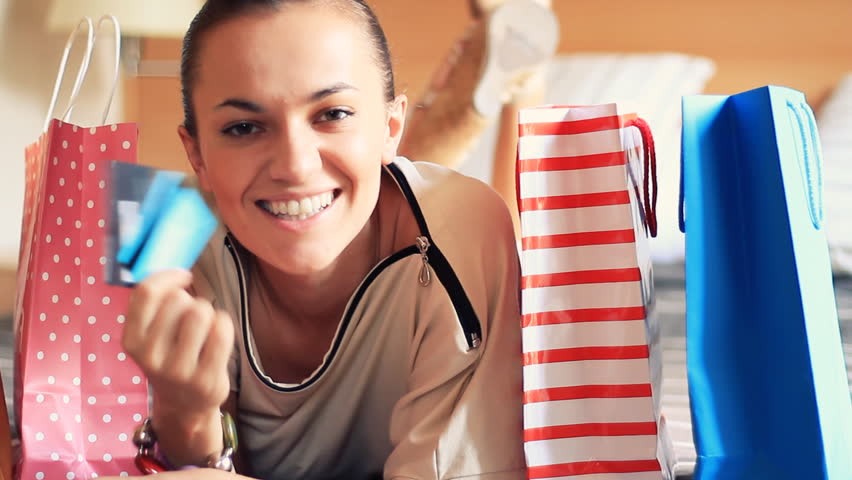 Portrait of smiling woman with shopping bags and credit card