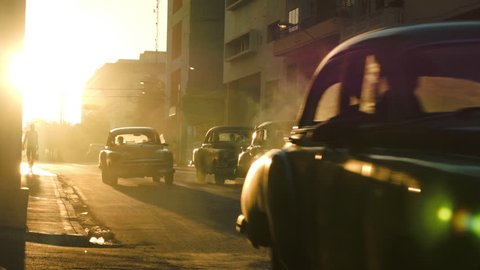 Row of classic cars in traffic during the sunset glow in Havana