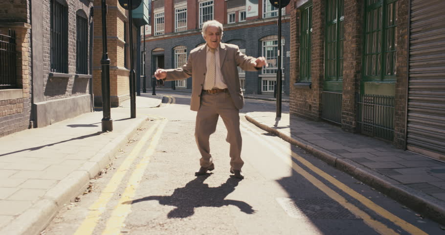 Happy elderly dancer man wearing suit funky street dancing freestyle in the city