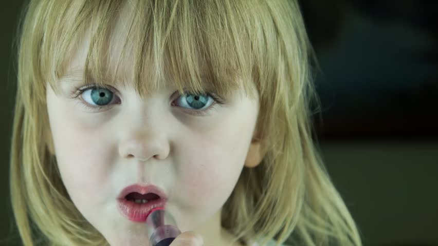 The little cute girl makes up lips with red lipstick and kisses on the camera