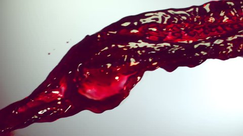 The stream red wine, grape juice, pomegranate juice, raspberry juice, cherry juice , slow motion, white background