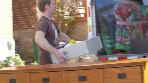 Man carrying drawers to moving truck