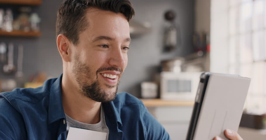Happy man at home sharing her ultrasound while talking to friends over internet using digital tablet app video excited to be a dad | Shutterstock HD Video #12707492