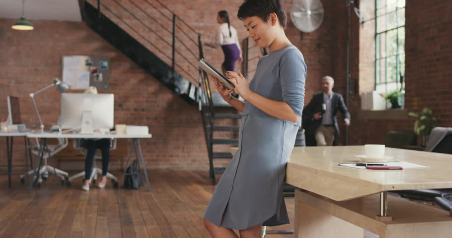 Stylish Asian Business woman using digital tablet in boardroom of trendy shared office space red brick interior